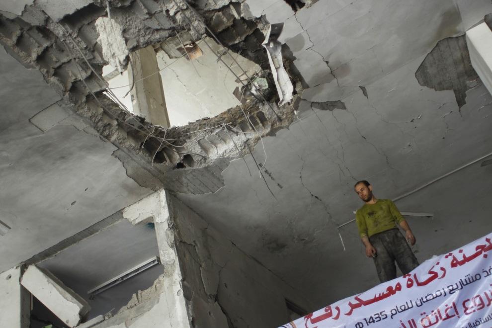 17.AUTONOMIA PALESTYŃSKA, Rafah, 15 lipca 2014: Palestyńczyk wewnątrz zniszczonego budynku należącego do jednej z organizacji dobroczynnych. AFP PHOTO / SAID   KHATIB