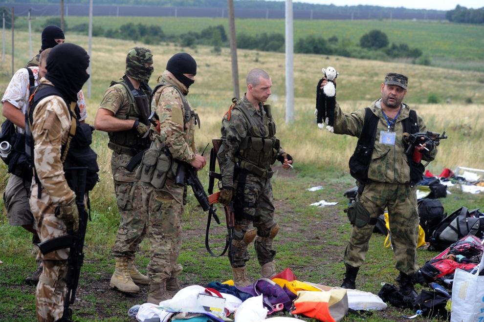 17.UKRAINA, Grabowo, 18 lipca 2014: Prorosyjscy separatyście przeglądają rzeczy znalezione w miejscu, gdzie spadł zestrzelony samolot. AFP PHOTO / DOMINIQUE FAGET