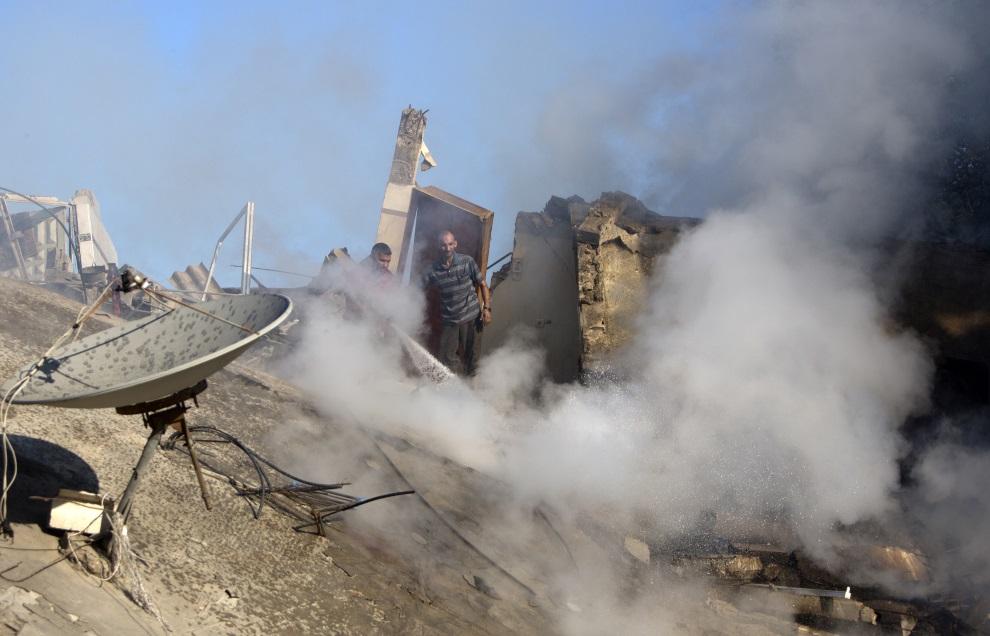 18.STREFA GAZY, 16 lipca 2014: Palestyński strażak dogasza ogień wywołany nalotem. AFP PHOTO / MAHMUD HAMS