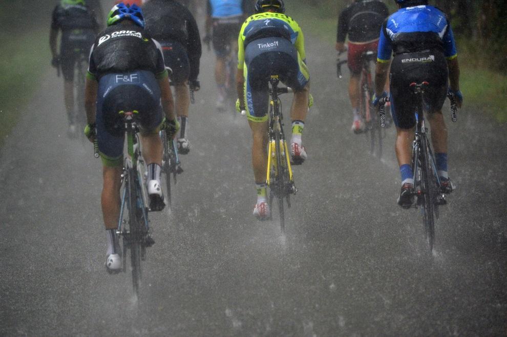 20.FRANCJA, Bergerac, 25 lipca 2014:  Kolarze w ulewnym deszczu podczas 19. etapu TDF. AFP PHOTO / LIONEL BONAVENTURE