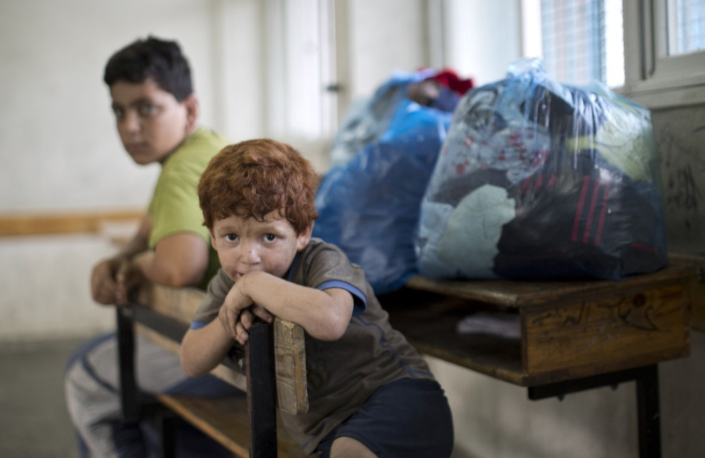 20.STREFA GAZY, 13 lipca 2014: Palestyńskie dzieci ewakuowane z domów w pobliżu granicy z z Izraelem. AFP PHOTO/MAHMUD HAMS