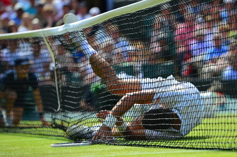 21.WIELKA BRYTANIA, Wimbledon, 2 lipca 2014: Novak Djokovic wpada na siatkę podczas meczu z Marinem Cilicem. AFP PHOTO / CARL COURT