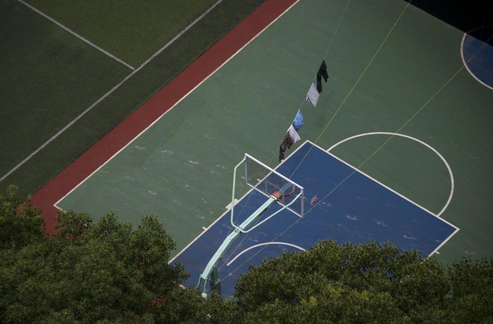 28.CHINY, Szanghaj, 17 lipca 2014: Ubrania suszące się nad boiskiem do koszykówki. AFP PHOTO / JOHANNES EISELE