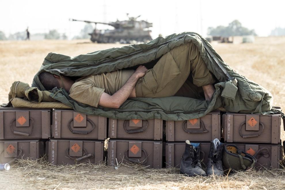 29.IZRAEL, (pogranicze), 11 lipca 2014: Izraelski żołnierz śpiący na skrzyniach z amunicją. AFP PHOTO / JACK GUEZ