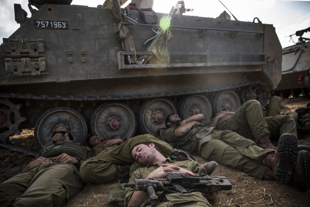 31.IZRAEL, Sderot, 15 lipca 2014: Izraelscy żołnierze śpiący przy transporterach opancerzonych. (Foto: Andrew Burton/Getty Images)