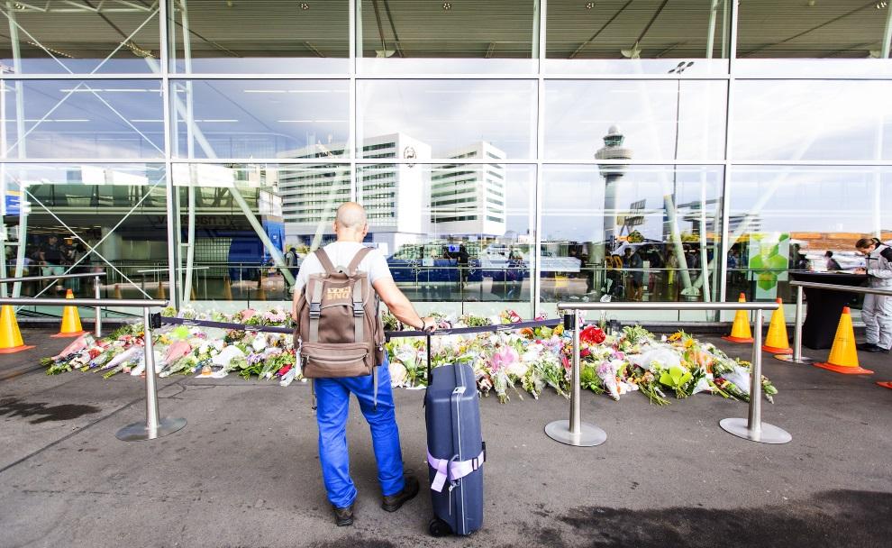 4.HOLANDIA, Schiphol, 20 lipca 2014: Podróżny patrzy na kwiaty złożone przed terminalem. AFP PHOTO / ANP / VALERIE KUYPERS
