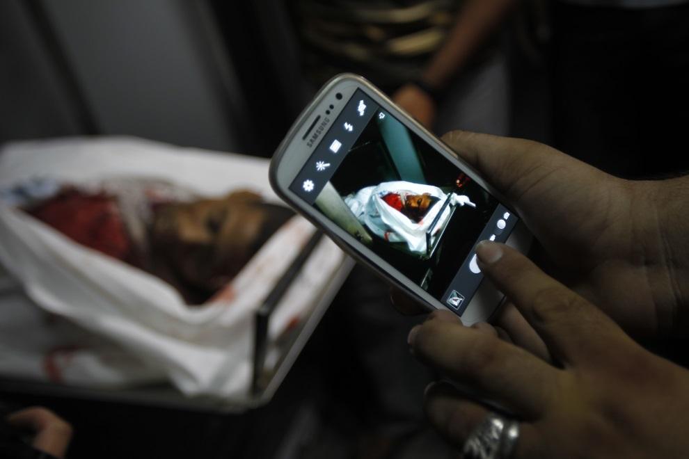 4.STREFA GAZY, Chan Junus , 29 czerwca 2014: Palestyńczyk robi zdjęcie mężczyźnie zabitemu w wyniku izraelskiego nalotu. AFP PHOTO / SAID KHATIB
