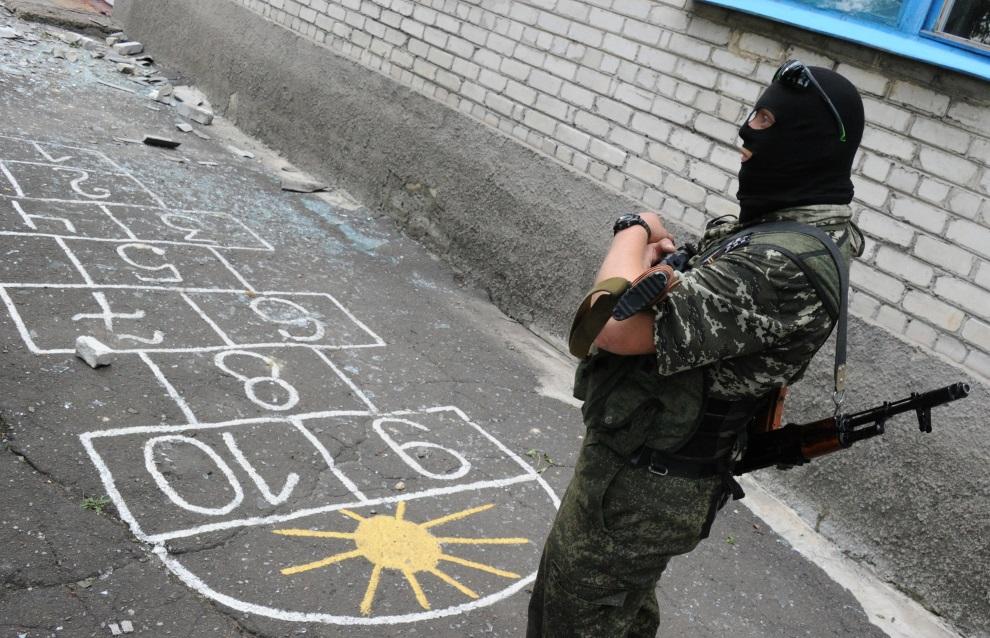 4.UKRAINA, Donieck, 15 lipca 2014: Prorosyjski separatysta na przedszkolnym podwórku. AFP PHOTO / DOMINIQUE FAGET