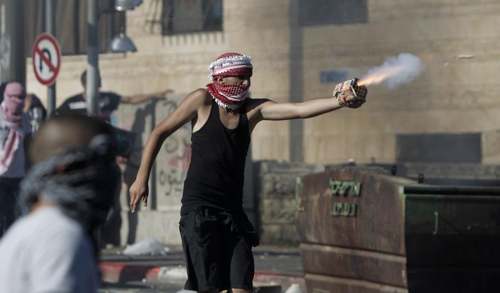 5.IZRAEL, Jerozolima, 2 lipca 2014: Palestyńczyk strzelający sztucznymi ogniami w kierunku izraelskich żołnierzy. AFP PHOTO / AHMAD GHARABLI