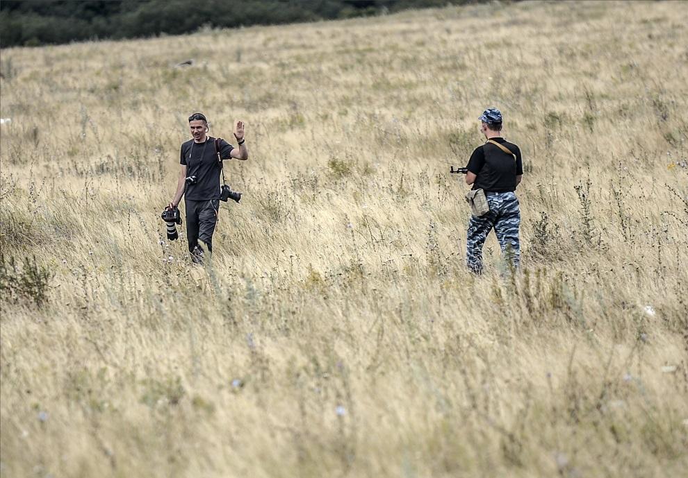 6.UKRAINA, Grabowo, 20 lipca 2014: Prorosyjski separatysta rozkazuje fotoreporterowi opuścić miejsce gdzie spadł zestrzelony MH17. AFP PHOTO/ BULENT KILIC