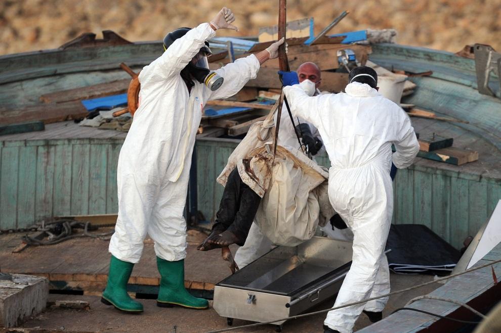 7.WŁOCHY, Pozzallo, 1 lipca 2014: Strażacy i policjanci wynoszą ciała uciekinierów z Afryki, odkryte na przechwyconej przez straż przybrzeżną łodzi. AFP PHOTO / GIOVANNI ISOLINO