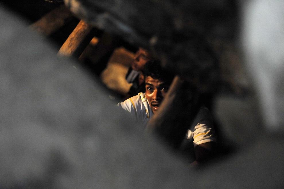 8.HONDURAS, Choluteca, 3 lipca 2014: Górnicy przeciskający się przez zawalony chodnik w kopalni. AFP PHOTO / ORLANDO SIERRA