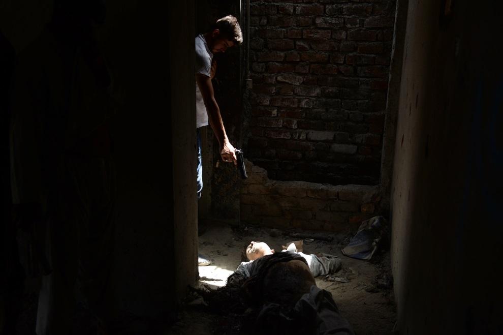 8.AFGANISTAN, Kabul, 17 lipca 2014: Afgański funkcjonariusz wywiadu celuje w ciało taliba zabitego podczas ataku rebeliantów na lotnisko w Kabulu.  AFP PHOTO/SHAH Marai