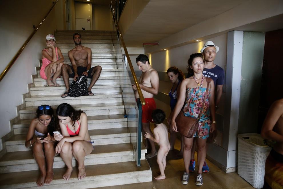 8.IZRAEL, Tel Awiw, 14 lipca 2014: Plażowicze chroniący się przed ostrzałem w pobliskim hotelu. AFP PHOTO/GALI TIBBON