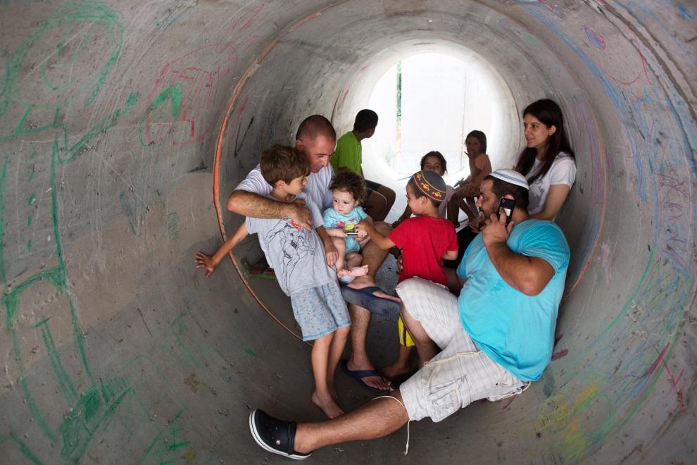 9.IZRAEL, Nitzan, 10 lipca 2014: Izraelczycy chroniący się przed ostrzałem. AFP PHOTO/MENAHEM KAHANA