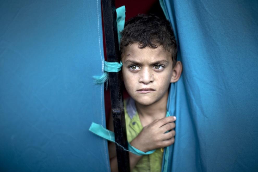 10.STREFA GAZY, 31 lipca 2014: Palestyński chłopiec mieszkający w obozie dla uchodźców.  AFP PHOTO / MAHMUD HAMS
