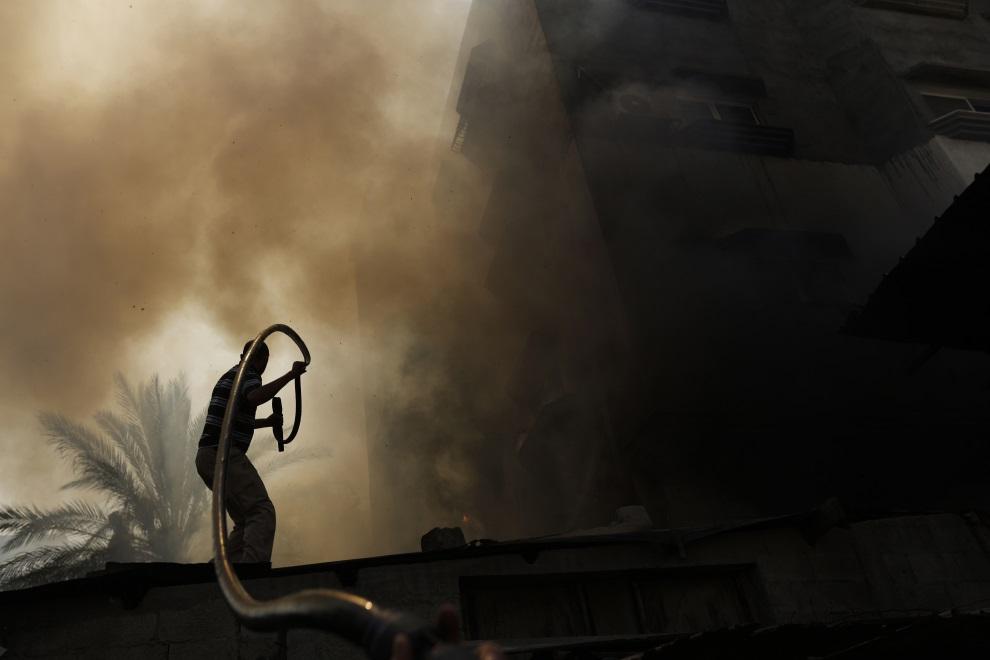 19.STREFA GAZY, 30 lipca 2014: Palestyńczyk starający się ugasić pożar wywołany izraelskim ostrzałem. AFP PHOTO / MOHAMMED ABED