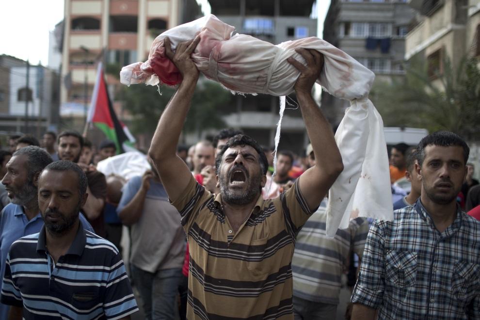 21.STREFA GAZY, Beit Lahia, 25 lipca 2014: Palestyńczyk z ciałem jednorocznego dziecka zabitego w wyniku izraelskiego ostrzału. AFP PHOTO/ MAHMUD HAMS