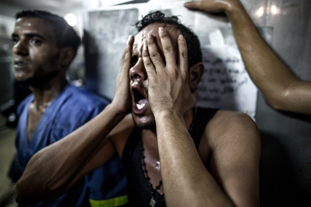 23.STREFA GAZY, 28 lipca 2014: Bliski trójki dzieci, które zginęły podczas izraelskiego ostrzału. AFP PHOTO/MARCO LONGARI