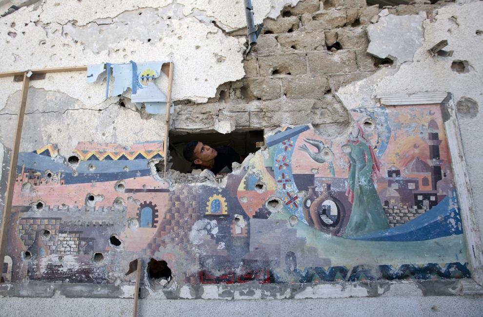 25.STREFA GAZY, 30 lipca 2014: Palestyńczyk sprawdza uszkodzenia budynku szkoły prowadzonej przez ONZ. AFP PHOTO/MAHMUD HAMS