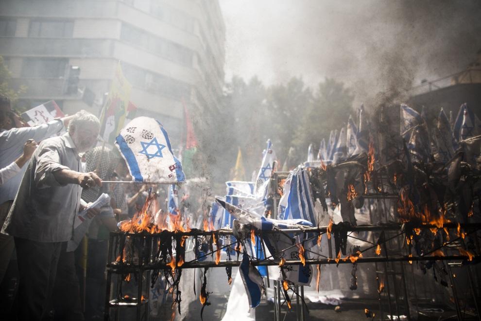 28.IRAN, Tehran, 25 lipca 2014: Izraelskie flagi palone podczas demonstracji w Teheranie. AFP PHOTO/BEHROUZ MEHRI