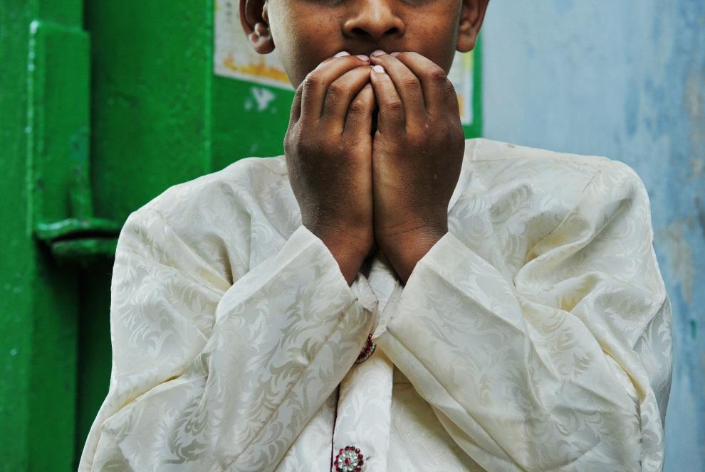 8.INDIE, New Delhi, 29 lipca 2014: Muzułmański chłopiec podczas modlitwy. AFP PHOTO/ROBERTO SCHMIDT