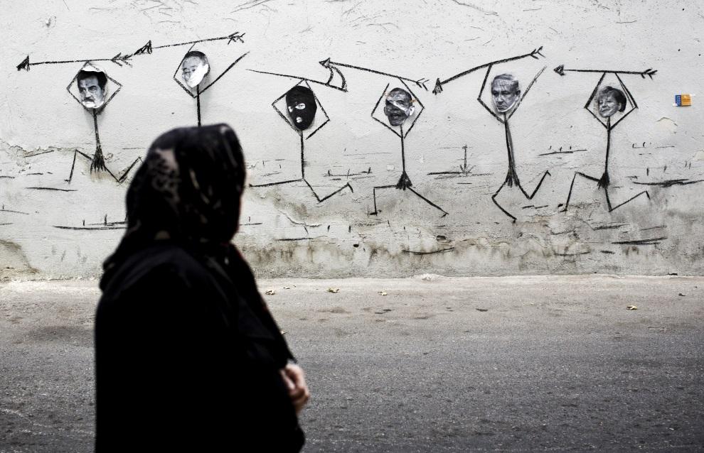 9.IRAN, Tehran, 29 lipca 2014: Mural w centrum Teheranu przedstawiający (od lewej):  Saddama Husseina, Ban Ki-moona, człowiek w kominiarce, Baracka Obamę,   Benjamina Netanyahu oraz Angelę Merkel. AFP PHOTO/BEHROUZ MEHRI