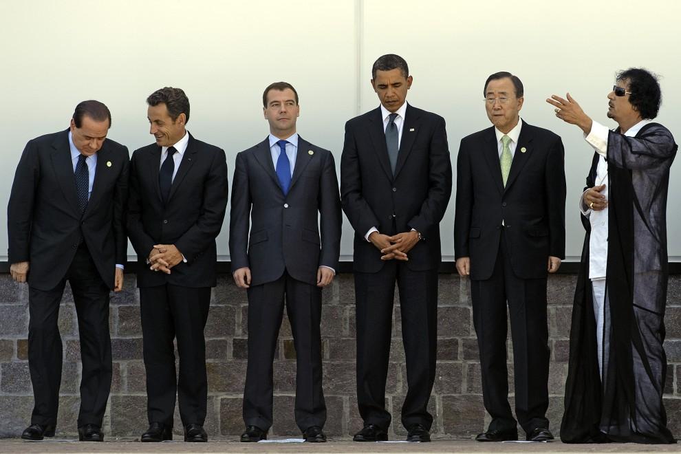 32. WŁOCHY, L'Aquila, 10 lipca 2009: Muammar al-Kaddafi  w towarzystwie innych polityków na szczycie G8. Stoją od lewej: premier Włoch Silvio Berlusconi,   prezydent Francji Nicolas Sarkozy, prezydent Rosji Dmitrij Miedwiediew, prezydent USA Barack Obama,  sekretarz generalny ONZ Ban Ki-moon. AFP PHOTO / JIM   WATSON